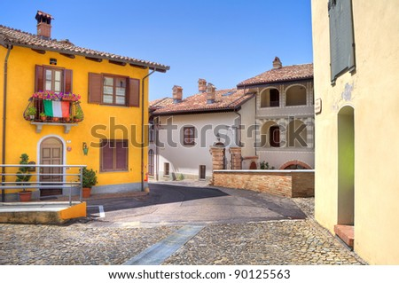 Narrow paved street among multicolored houses in town of Castiglione Falletto, Northern Italy.