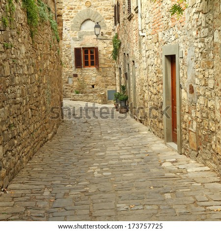 narrow  paved street and stone walls in italian village, borgo Montefioralle, Tuscany - stock photo