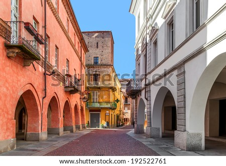 Narrow paved street between old medieval and renewed buildings in town of Alba in Piedmont, Northern Italy. - stock photo