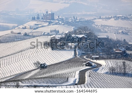 Narrow road through hills and vineyards covered with snow towards small village in Piedmont, Northern Italy. - stock photo