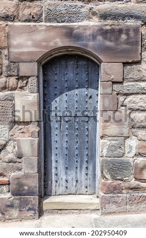 Narrow Rustic worn Medieval Door set in old sandstone wall. - stock photo