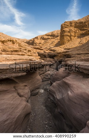 Narrow slot between two striped orange rocks in Red Canyon, Israel