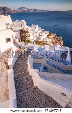 Narrow step path going down in Oia city, Santorini, Greece on a sunny day - stock photo