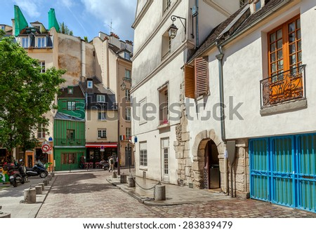 Narrow street among typical parisian buildings in Paris, France.