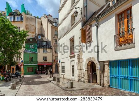 Narrow street among typical parisian buildings in Paris, France. - stock photo