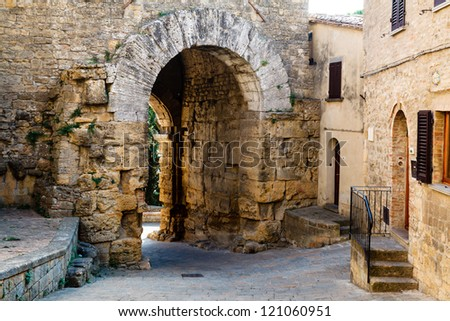 Narrow Street and Ancient Etruscan Gate of Volterra in Italy - stock photo