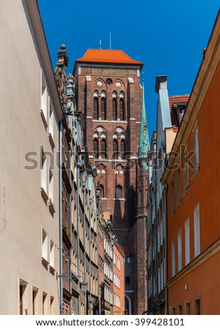 Narrow street and Basilica of the Assumption of the Blessed Virgin Mary in Main City of Gdansk, Poland - stock photo