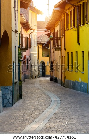 Narrow street between italian houses in old town of Novara, Toning. - stock photo