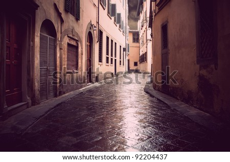 Narrow street in Florence on a rainy day, with vintage look - stock photo