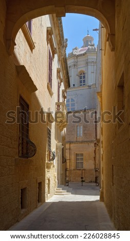 Narrow street in Mdina, the old capital of Malta, with view to St. Paul's cathedral - stock photo