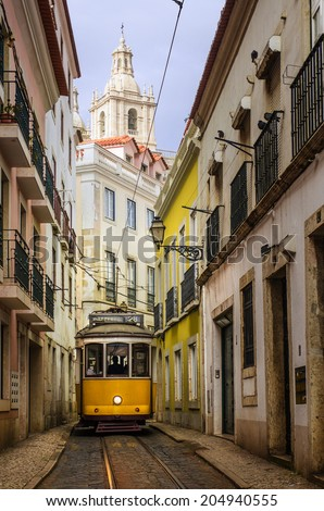 Narrow street in old Lisbon downtown with typical yellow tram - stock photo