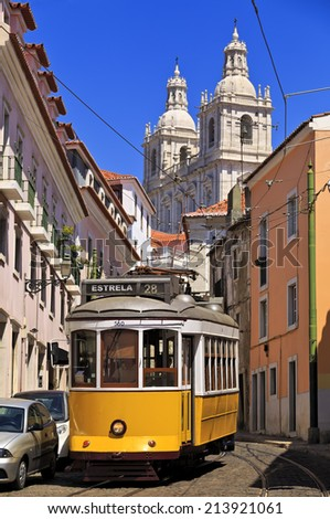 Narrow street in old Lisbon downtown with typical yellow tram, Portugal - stock photo