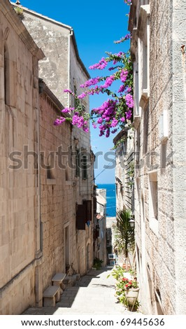 Narrow street in old medieval town Korcula by suny day. Croatia, Dalmatia region, Europe. - stock photo