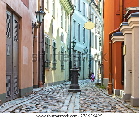 Narrow street in old Riga city, Latvia. Riga is the capital and largest city of Latvia, a major commercial, cultural, historical and financial center of the Baltic region - stock photo