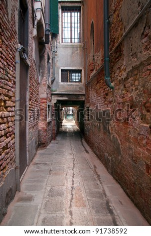 Narrow street in Venice, Italy, ending at a getty in a canal - stock photo