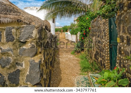 Narrow street of african village on NGor island with black lava stone masonry walls composed of various-shaped rocks and exotic plants - stock photo