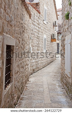 narrow street of old stone Mediterranean city - stock photo