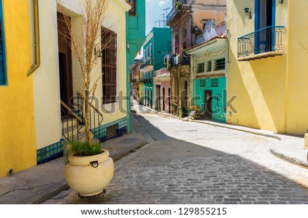Narrow street sidelined by colorful buildings in Old Havana - stock photo