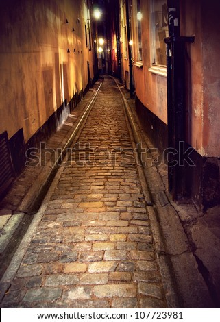 Narrow street with cobblestones in old town of stockholm at night - stock photo