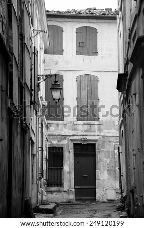 Narrow the street in Arles (Provence, France). Weathered stucco walls, red wooden shutters and forging lanterns. Aged photo. Black and white.