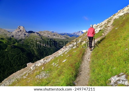 Narrow trail ascending along Tofana massif and isolated hiker early in the morning, Dolomite Alps, Italy - stock photo