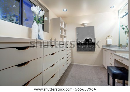 Narrow Walk In Closet Features Make Up Vanity Finished With An Oval Sink Alongside Built