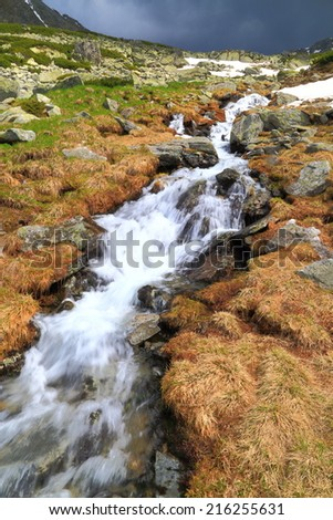 Narrow water flowing rapidly over the rocks under cloudy sky - stock photo