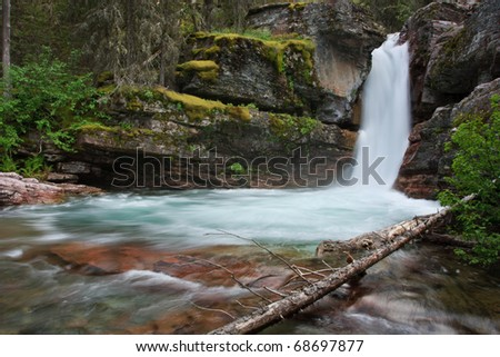 Narrow waterfall passes through rocky moss covered gorge in Glacier National Park, Montana. - stock photo