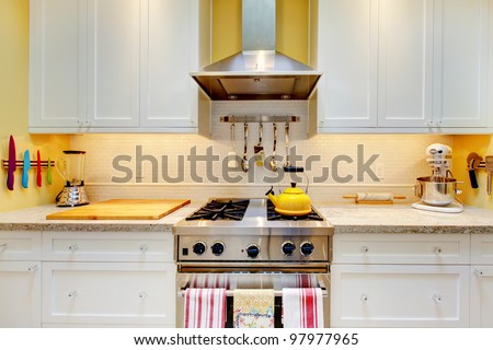 Narrow white and yellow kitchen with cabinets close up. - stock photo
