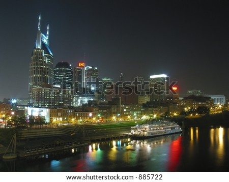 Nashville skyline at night with riverboat