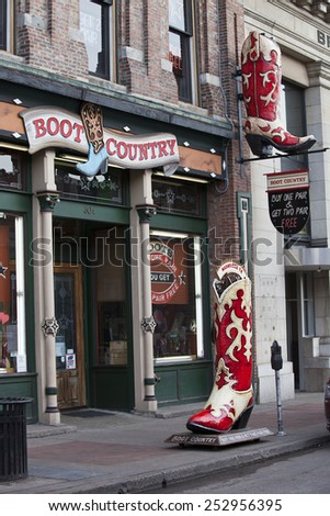 NASHVILLE, TENNESSEE-FEBRUARY 4, 2015:  Broadway Street in Nashville, Tennessee is the hub of the Honky Tonk district.  Cowboy boots are a featured item. - stock photo