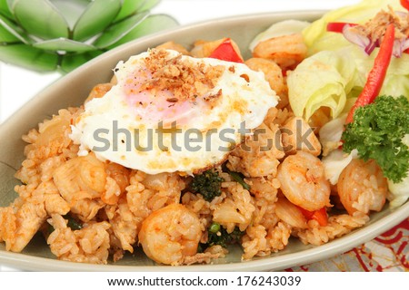 Nasi Goreng, Indonesian fried rice/Nasi Goreng/A close up photo of Indonesian fried rice also known as Nasi Goreng with Batik napkin and lotus flower. - stock photo