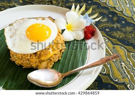 Nasi Goreng, Indonesian fried rice plate, on the Batik cloth. - stock photo
