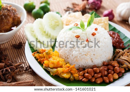 Nasi lemak kukus traditional malaysian spicy rice dish, fresh cooked with hot steam. Served with belacan, ikan bilis, acar, peanuts and cucumber. Decoration setup. - stock photo