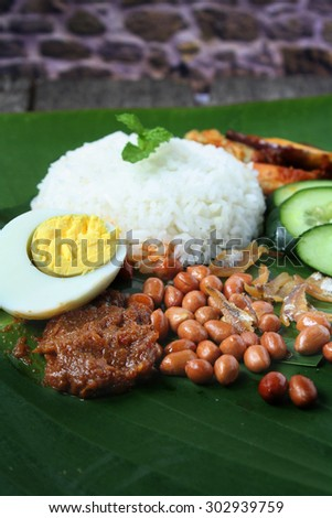 Nasi Lemak-Malaysian cuisine.  A fragrant rice dish cooked in coconut milk and pandan leaf commonly found in Malaysia. Served with sambal, anchovies, peanut and cucumber. - stock photo