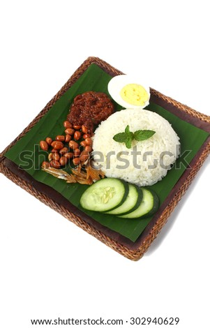 Nasi Lemak. Malaysian cuisine. Nasi lemak is a fragrant rice dish cooked in coconut milk and pandan leaf. Served with sambal, peanut, anchovies and cucumber - stock photo