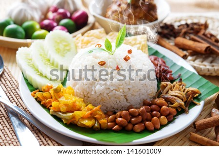 Nasi lemak traditional malaysian hot and spicy rice dish, fresh cooked with hot steam. Served with belacan, ikan bilis, acar, peanuts and cucumber. Decoration setup. - stock photo