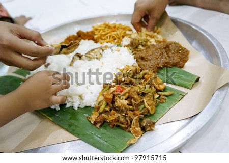 Nasik Ambeng, famous dish from Java served in big plate and shared by 3 people (shallow depth of field) - stock photo