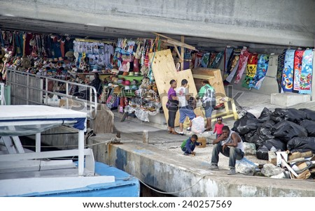 NASSAU, BAHAMAS, DECEMBER 2, 2014: Flea market under the bridge that connects Nassau and the exclusive Paradise Island as the holiday season begins. A contrast between the rich and poor. - stock photo
