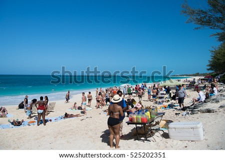 Nassau, Bahamas-March 09, 2016: summer beach with people sunburn on white sand during vacation with blue sky and sea water on sunny coast on natural background