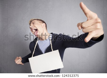 Nasty provocative man holding white empty signboard with space for text isolated on grey background. - stock photo