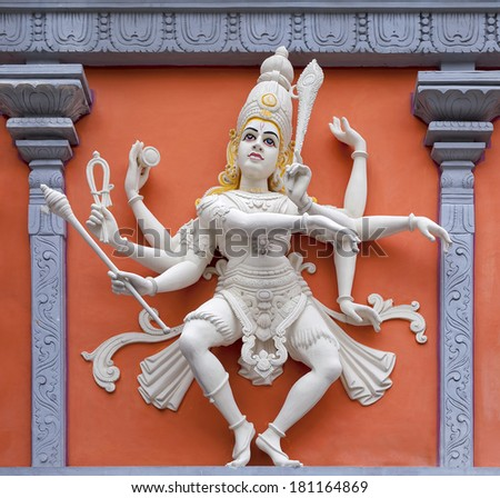 Nataraj Dancing Form of Lord Shiva Hindu God Orange and White Statue on Temple Exterior Wall Relief - stock photo