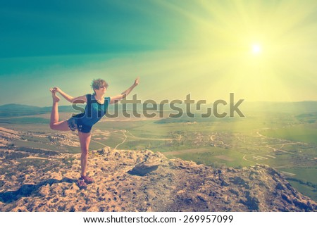 Nataraja asana by young woman high in the mountains - instagram style - stock photo