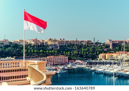 National flag of of the Principality of Monaco and view of port - stock photo