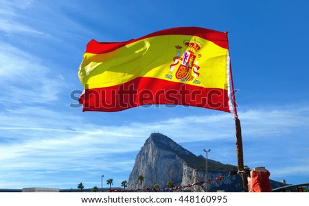 National Flag of Spain ( from back side ) fluttering in wind, the rock of Gibraltar in background. - stock photo