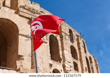 National flag of Tunisia on Tunisian Amphitheatre background in El Djem, Mahdia - stock photo