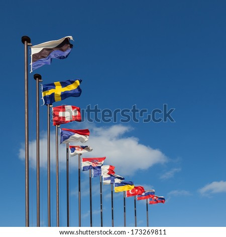 National flags of different countries on a background of blue sky - stock photo