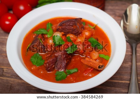National Greek dish stifado with beef, tomatoes and onions, stewed in red wine with Herbs on a wooden background, horizontal