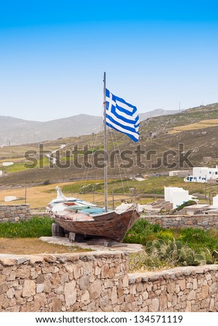 National old fishing boat with the Greek flag. Mykonos. - stock photo