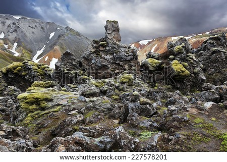 National Park Landmannalaugar in Iceland. Pieces of gray and black lava bizarre shapes, sometimes covered with green moss - stock photo